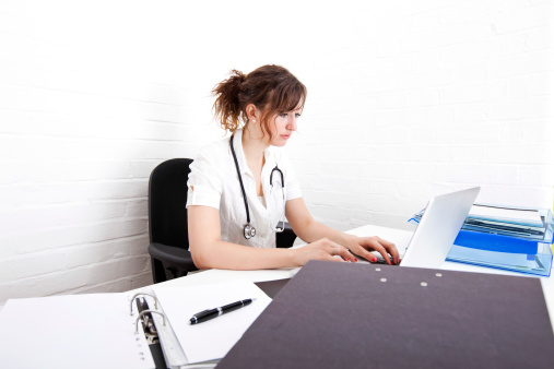 Young Female Doctor Using Laptop At Desk In Clinic ストックフォト | Thinkstock